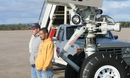 A couple of rather serious faced coworkers standing in front of our B747SP's nose landing gear for a photo op.