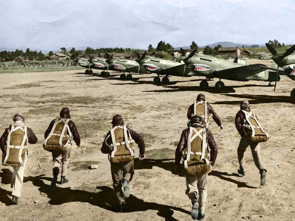 A colourised photo of pilots of the American Volunteer Group (AVG aka The Flying Tigers) running to their P-40…