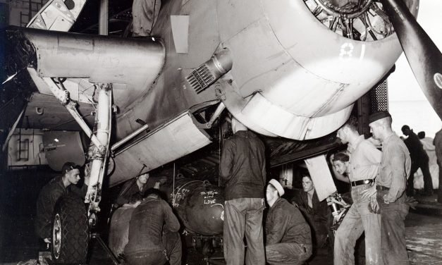 Ordinancemen loading a 1,000-pound bomb into the bombay of a TBM-1C aboard USS Intrepid, 1943-1945; note flame…