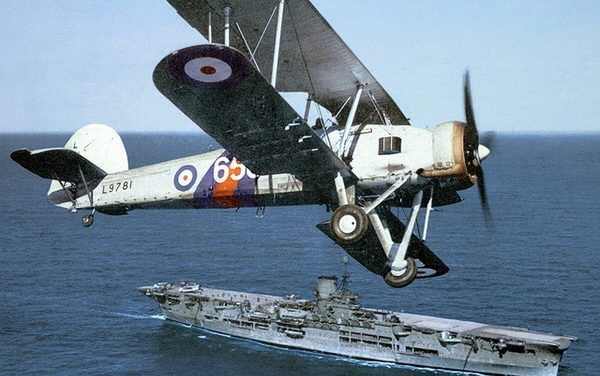 A Fairey Swordfish flies over HMS Ark Royal, 1939.