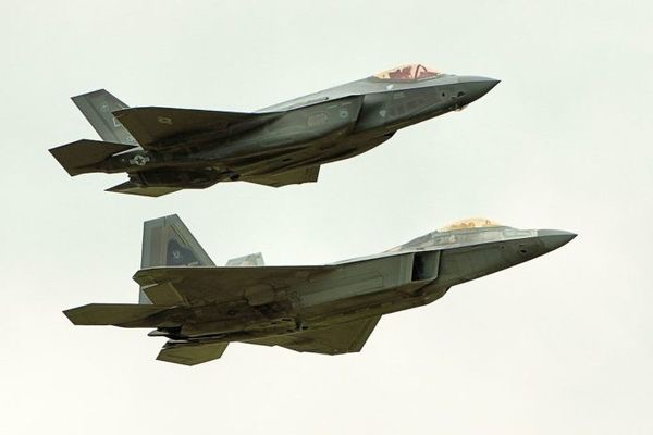 Two generations of stealth fighters- an F-22 Raptor (furthest from the camera) in formation with an F-35 Lightning…