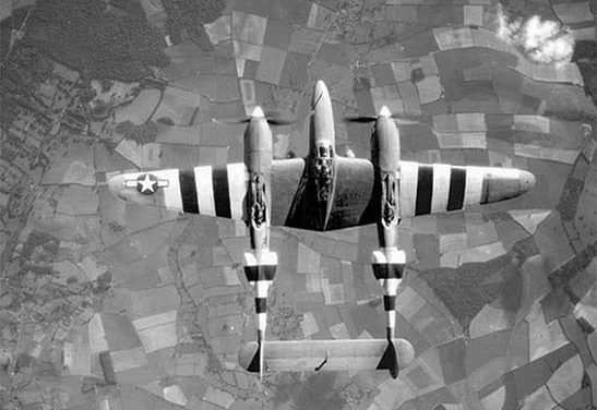 Top view of a P-38 Lightning aircraft in flight over the English countryside, June 1944.